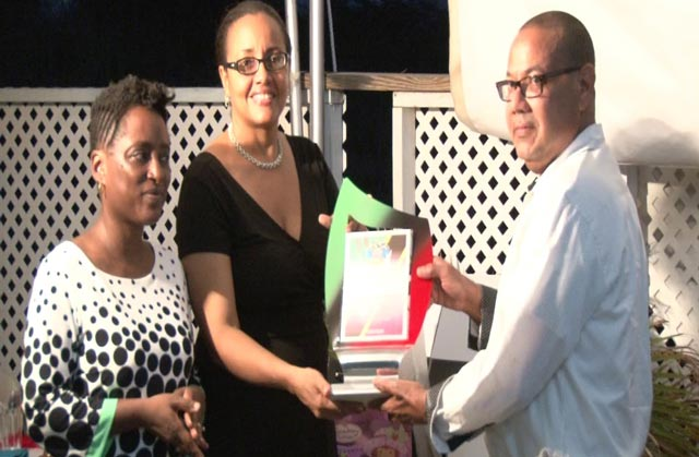 (From left) Permanent Secretary Janelle Lews Tafari looks on as Min. of State Wendy Phipps presents plaque to Valentine Monish, Marketing-Automotive Executive of L. S. Hosford whose company was the largest donor to Social Services for 2015-2016